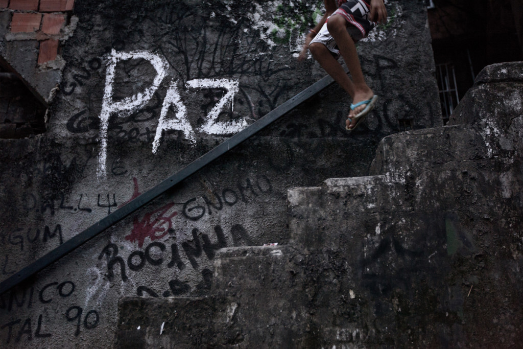 "A youth jumps down a stairway with the word ""peace"" written on the wall, in the Shantytown of Rocinha, the biggest slum of Rio de Janeiro, Brazil, February 22, 2012. Initiated in 2008, the UPP, short for Unidade de Polícia Pacificadora (in English, Pacifier Police Unit or Police Pacification Unit), is a new system of community policing in Rio de Janeiro's favelas once run by drug traffickers.  While many believe that UPPs have helped quell violence by opening the doors of the favelas to public services such as legal electricity supply, garbage collection, education, public works and social assistance program, others see the pacification program as a temporary cover-up to security problems in Rio de Janeiro."